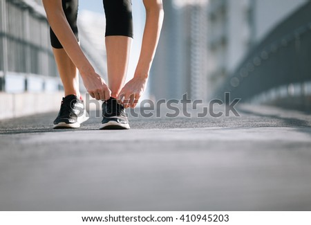 Time to workout. Young woman in the city getting ready for a run.  - stock photo
