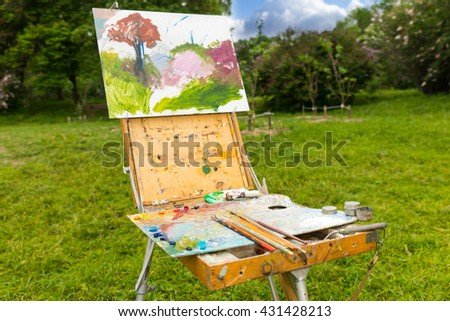 Time-worn professional painter's sketchbook  with different artist's equipment colorful palette paletteknife paints and paintbrushes outdoors - stock photo