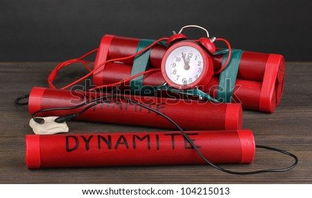 Timebomb made of dynamite on wooden table on grey background - stock photo