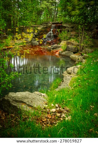 Timed exposure of a small, beautiful grotto-like rocky waterfall oasis and pond surrounded by the deep green of a lush, paradise-like forest. - stock photo