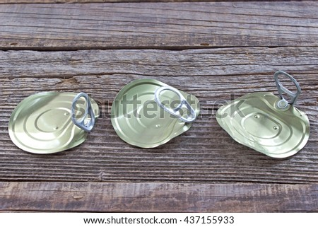Tin can lids with opener on wooden background - stock photo