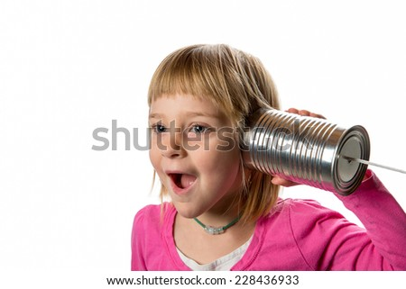 Tin Can Phone - Surprise.  Young girl listening to tin can / string phone.  Expressing surprise.  Isolated against a white background.  Copy space to left. - stock photo