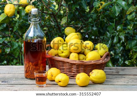 Tincture of quince and fruit in wicker basket on a wooden table. - stock photo