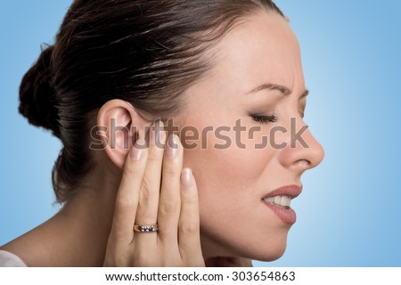 Tinnitus. Closeup up side profile sick young female having ear pain touching her painful head isolated on blue background - stock photo