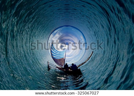 Tinny little planet concept. Fisherman in silhouette  - stock photo