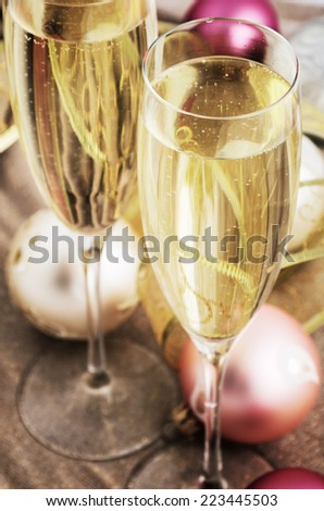 tinted image two glasses with champagne and Christmas tree decorations on the table. close-up shot from above, vertical - stock photo