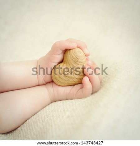 tiny baby hands to hold the wooden heart - stock photo