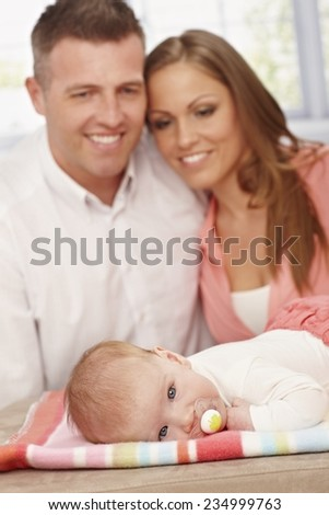 Tiny baby relaxing with dummy in mouth, parents adoring her from background. - stock photo