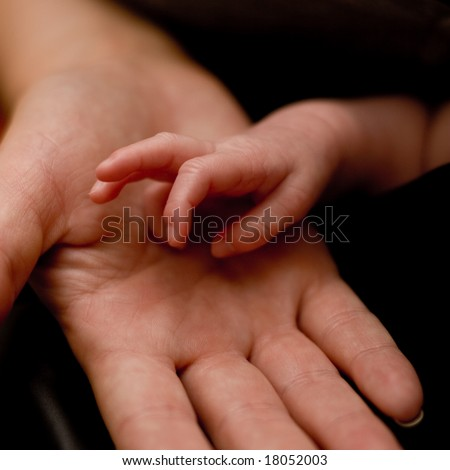 Tiny baby's hand in her father's hand - stock photo