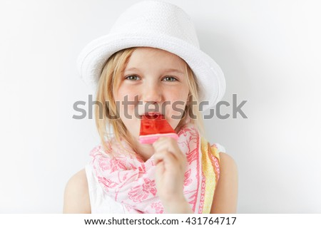 Tiny blond girl in summer hat sucking her sugar candy on stick with enormous pleasure. Bringing joy to little children is a good way to happy family life and friendly relationships. - stock photo