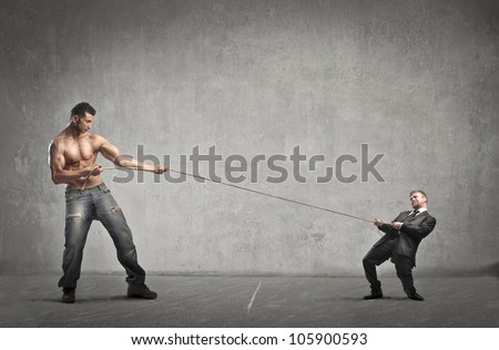 Tiny businessman and giant muscular man playing tug of war - stock photo
