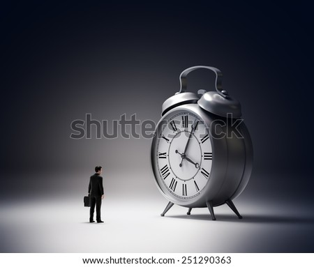 Tiny businessmen next to an alarm clock - stock photo
