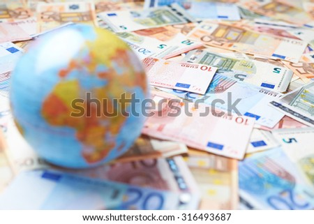 Tiny Earth globe over the surface covered with the multiple bank note bills, shallow depth of field composition - stock photo