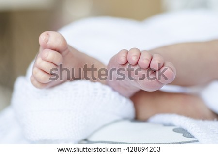 tiny foot of newborn baby. Focused on feet - stock photo