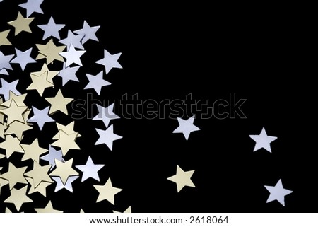 Tiny golden and silver stars isolated on black background. Space for copy. - stock photo