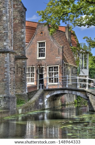 Tiny historical house and stone bridge along a canal in Delft, Holland - stock photo