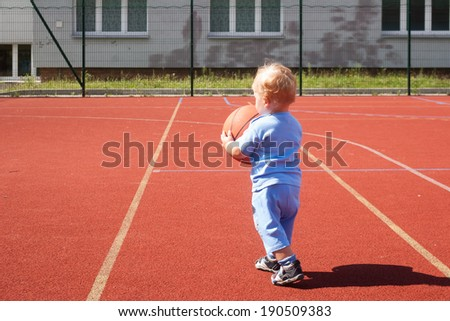 tiny little boy playing with a basketball  - stock photo