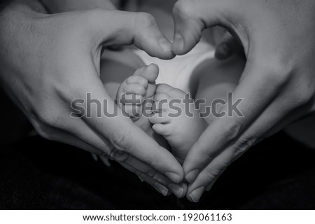 Tiny Newborn Baby`s feet being held by father's hand. - stock photo