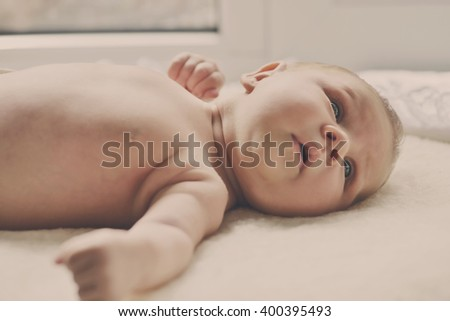tiny newborn with open eyes on the cover dresser - stock photo