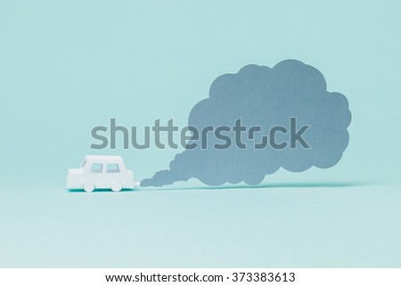 Tiny paper car and smoke on blue background. - stock photo