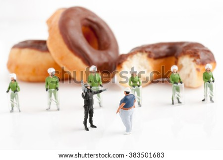 Tiny police in riot gear preventing an overweight man from reaching donuts a public health obesity concept selective focus on foreground figures - stock photo
