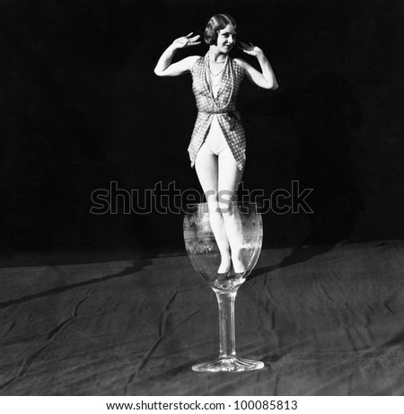 Tiny woman standing in wineglass - stock photo