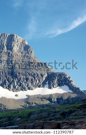 Tip of a mountain with a small glacier at the base. Photo taken at Glacier National Park in Montana, USA.  Photo taken in August 2012. - stock photo