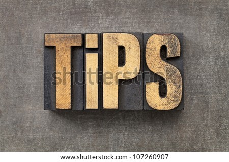 tips word - text in vintage letterpress wood type against a grunge metal sheet - stock photo