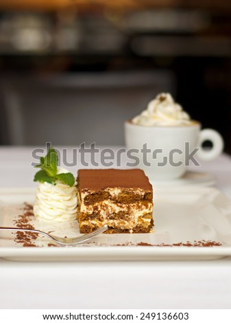 Tiramisu cake - delicious dessert served with whipped cream and a cup of cappuccino - stock photo