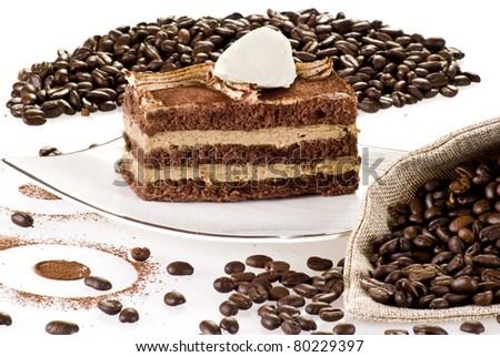 Tiramisu cake on the plate with coffee beans around - stock photo