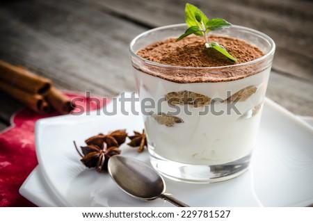 Tiramisu in the glass on the wooden background - stock photo