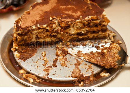 Tiramisu is made of biscuits dipped in coffee, layered with a whipped mixture of egg yolks and mascarpone, and flavored with liquor and cocoa. - stock photo