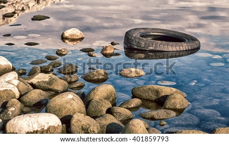 Tire in lake. Environmntal  protection. Water pollution. - stock photo