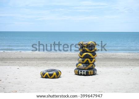tire inner tubes on the beach - stock photo