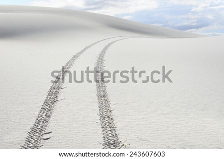 Tire Tracks Across White Sand Dunes - stock photo