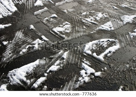 Tire tracks in the melting snow on asphalt road - stock photo