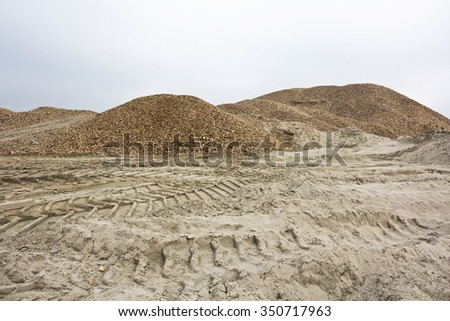 Tire tracks in the sand and gravel hills. - stock photo