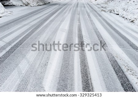 tire tracks on the road after snow - stock photo