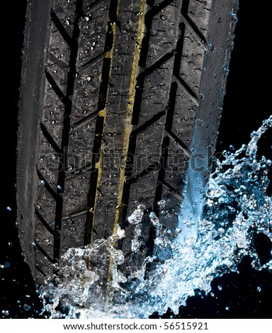 Tire with water drops on it black background - stock photo