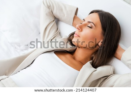 Tired after hard working day. Top view of beautiful young businesswoman in suit holding hands behind head and keeping eyes closed while lying in bed at the hotel room  - stock photo