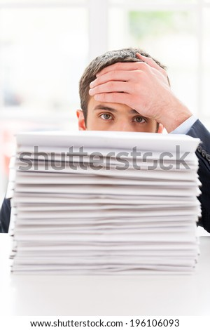 Tired and overworked. Depressed young man in shirt and tie looking out of the stack of documents laying on the table and touching his forehead with hand - stock photo