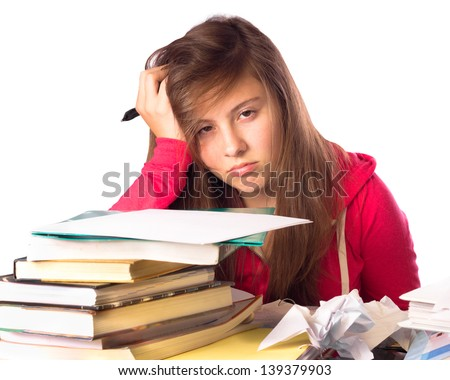 Tired and stressed teenage girl surrounded by books doing homework - stock photo