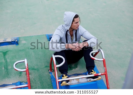 Tired athlete resting after abdominal crunches sitting near training apparatus, young handsome man runner took a break after warm up exercising, sportsman engaged in physical activity at street gym - stock photo