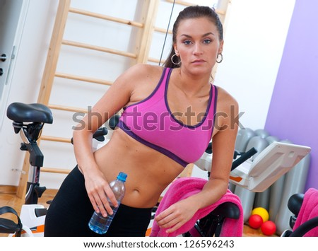 tired attractive woman in gym after workout with water bottle - stock photo