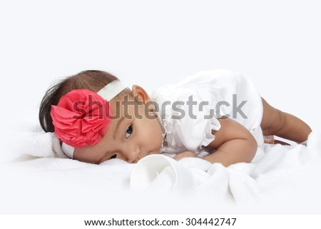 Tired baby lying in bed with sleepy eye, isolated on white background - stock photo