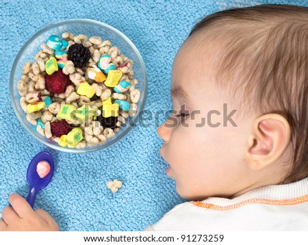 Tired Baby sleeping beside full bowl of cereal - stock photo