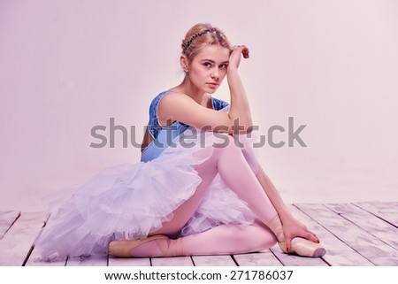 Tired ballet dancer sitting on the wooden floor on a pink background - stock photo