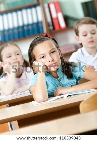 Tired beautiful schoolgirl sits at the desk and leans on her hand - stock photo
