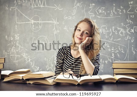 Tired blonde student on her desk with many books - stock photo