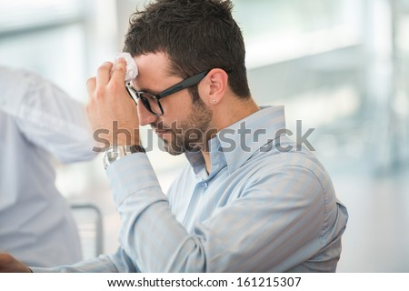 Tired business man with glasses wiping his forehead - stock photo